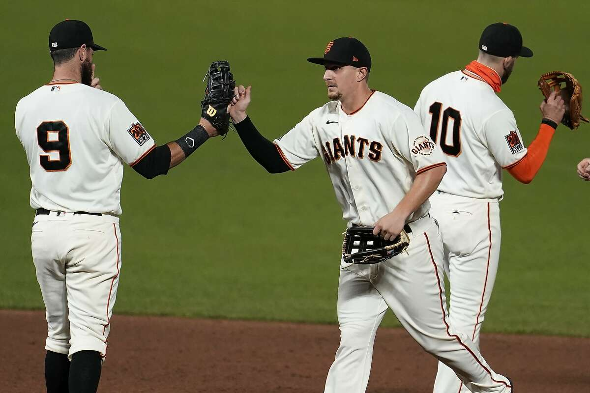 San Francisco Giants' Brandon Belt, left, celebrates with Alex Dickerson and Evan Longoria, right, after the Giants defeated the Colorado Rockies 5-2 in a baseball game in San Francisco, Tuesday, Sept. 22, 2020.