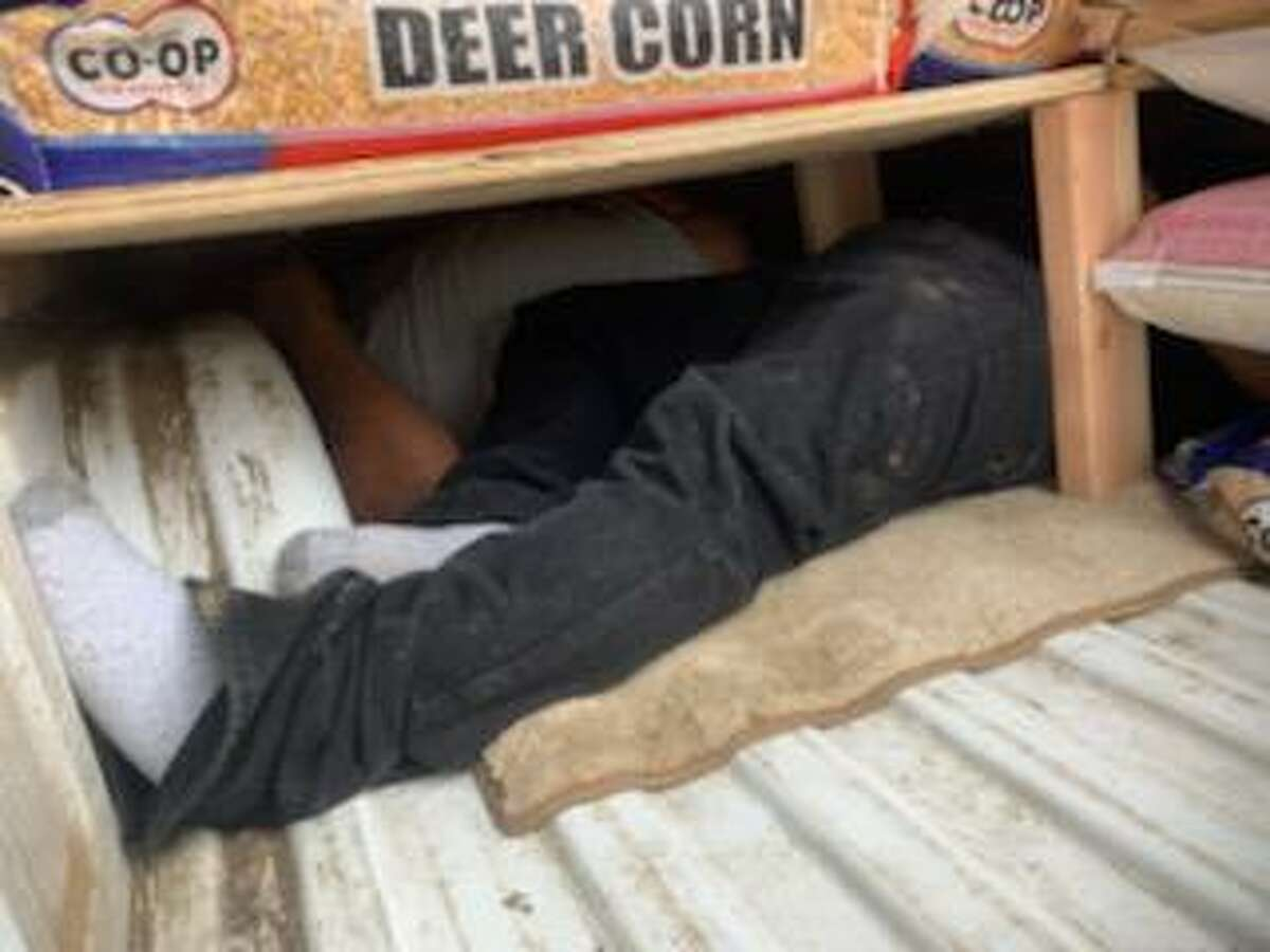People can be seen inside a compartment that was hidden underneath bags of deer corn, horse feed and dog food. U.S. Border Patrol agents discovered four individuals who had crossed the border illegally.