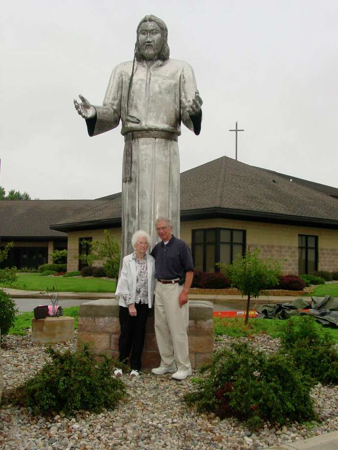 Emily Allen and her son Ernie of Midland pose with the statue of Jesus Christ in front of Messiah Lutheran Church. Ernie and his friend Jim Leigeb worked on the statue for over a year to present to the church. (Photo provided/Facebook)