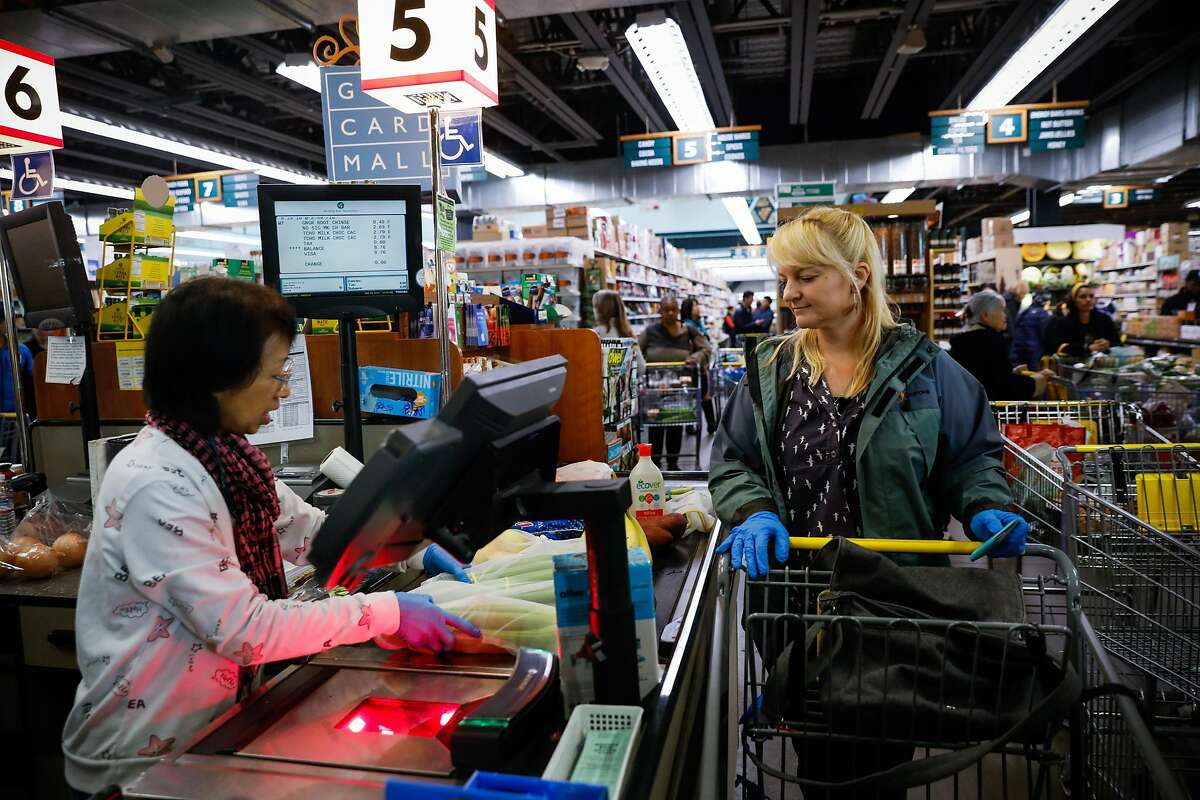"""Oakland resident Shannon Ratay checks out at Berkeley Bowl on Sunday, March 15, 2020 in Berkeley, California. In a unanimous vote Tuesday night, the Berkeley City Council passed the """"healthy checkout"""" bill, eliminating the sale of junk food and beverages in the checkout lane and requiring healthy food options instead starting next year."""