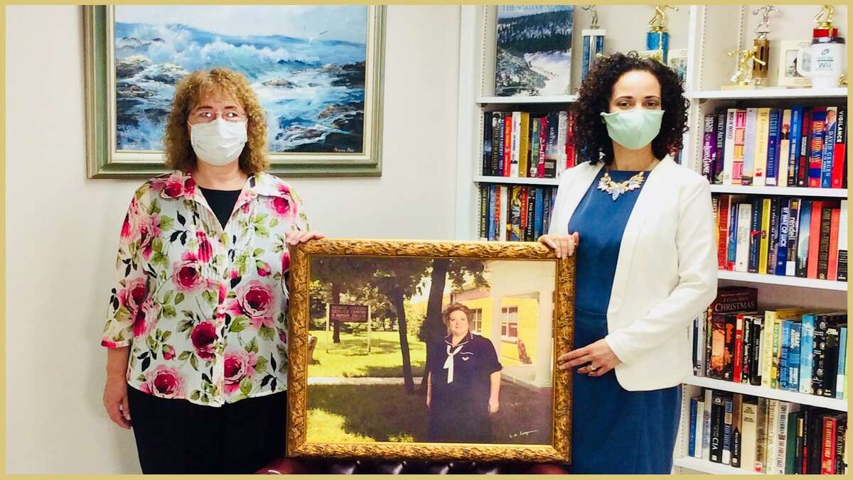Milford Senior Center's retired executive director, Janice M. Jackson, and Leonora Rodriguez, current executive director, hold a framed photo of the center's founding director, Kathi Bissell, who died in 2004.