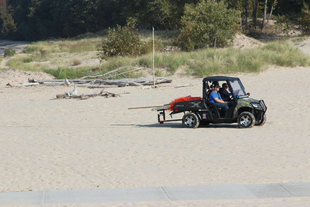 Frankfort Fire and Rescue use an ATV to move equipment after areas of the beach and pier were closed to the public during the search and recovery of a body on Sept. 23.