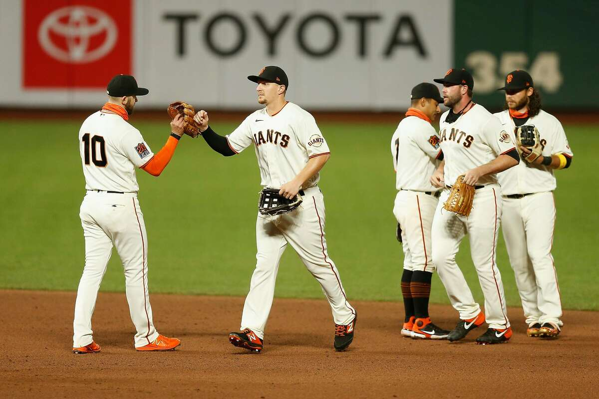 Giants players congratulate each other after Tuesday night's win which kept them in National League playoff contention.