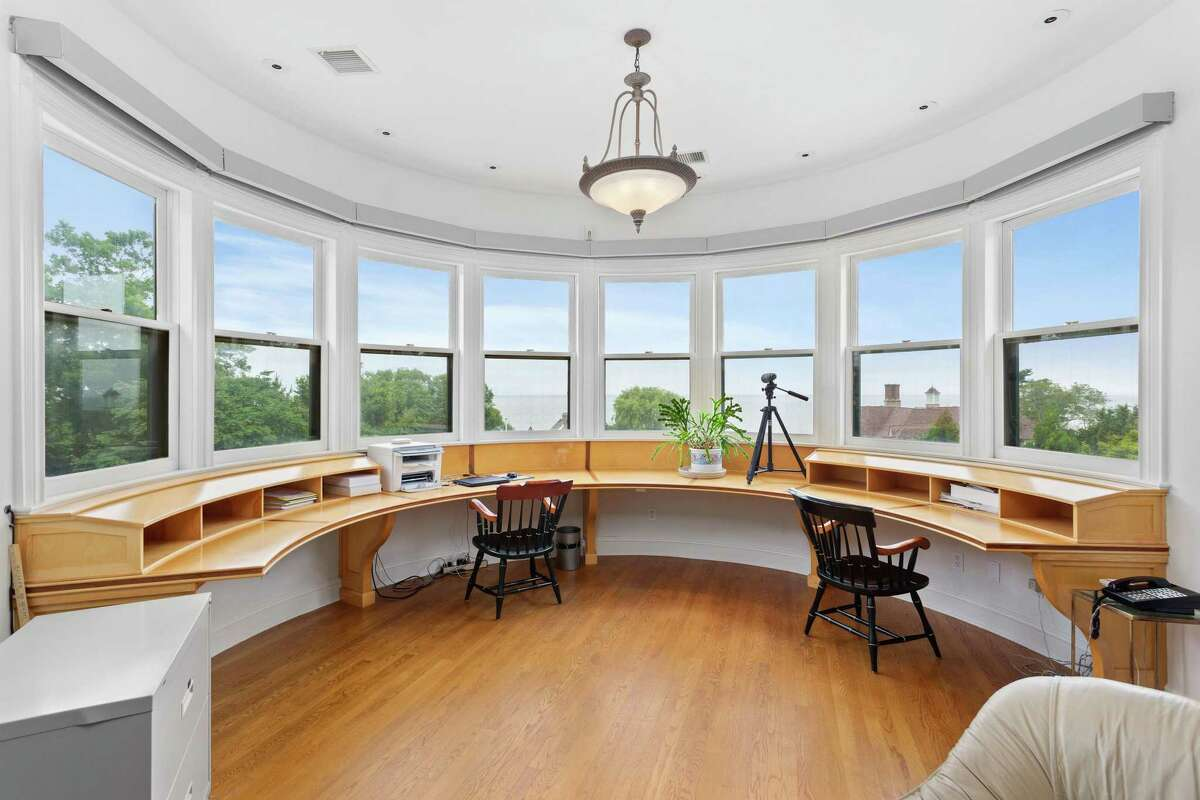 In one turret there is an office with a rounded wall of windows and a built-in rounded desk that can accommodate at least two people.
