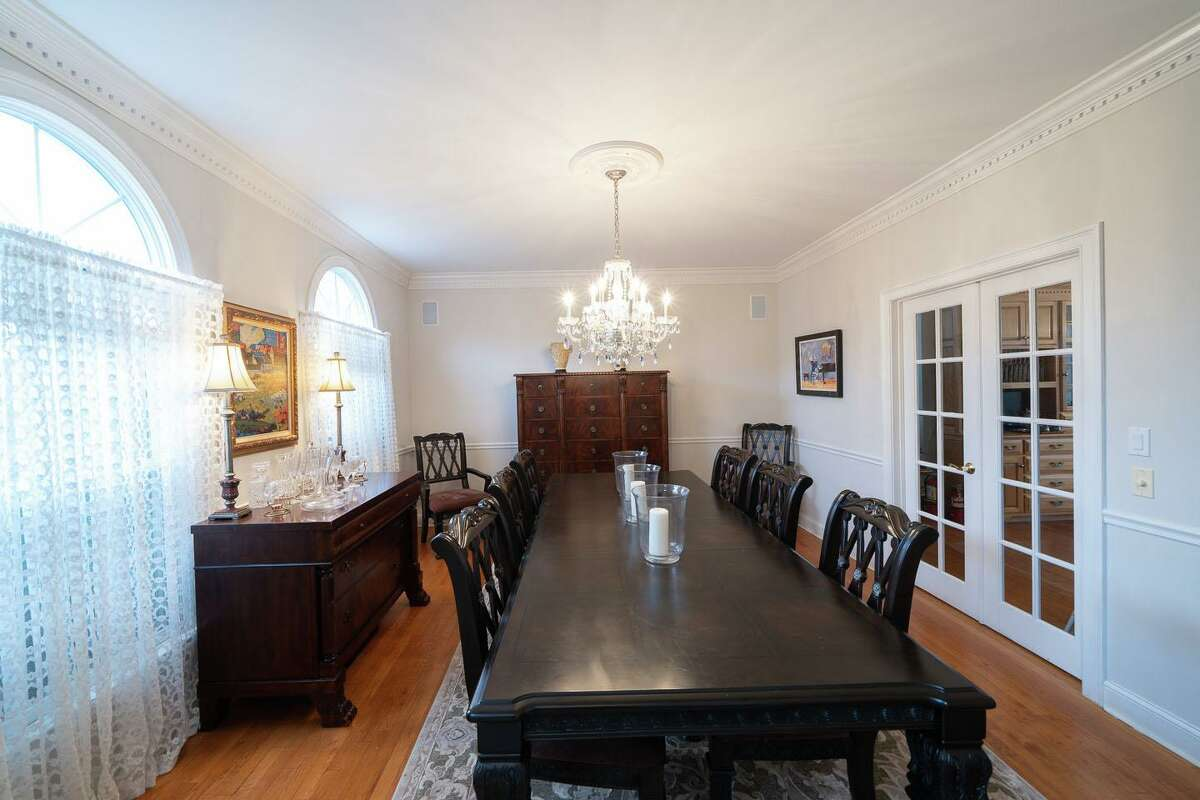 In the formal dining room there is dentil crown molding, chair railing, and French doors separating it from kitchen.