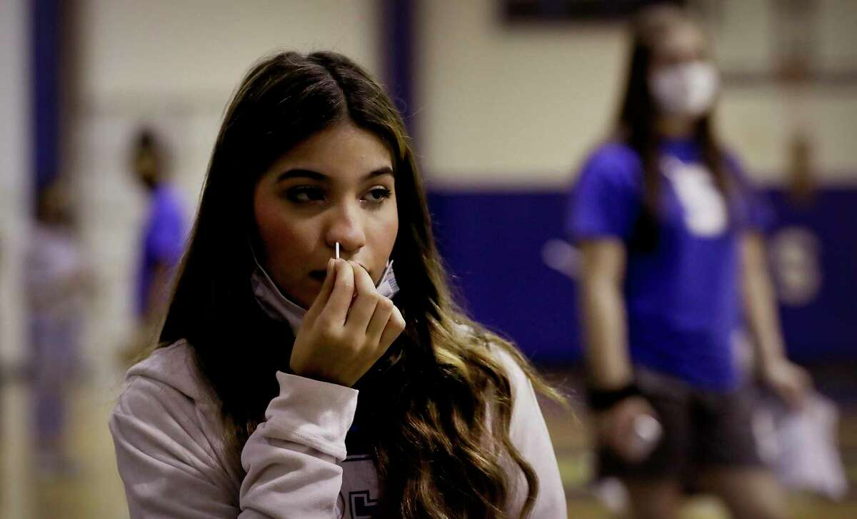 Sophomore Monique Perez, a member of the cheer team and track team at Somerset High School, performs a coronavirus test at Somerset High School on Wednesday, participating in a pilot program for mass testing developed by the startup non-profit Community Labs.