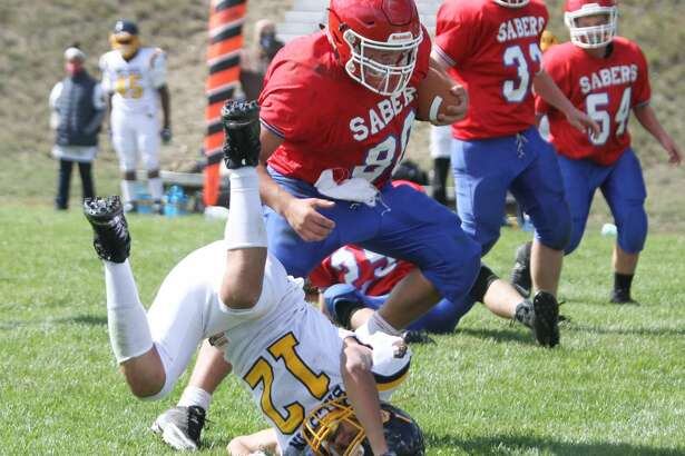 Manistee Catholic Central quarterback Justin Stickney breaks a tackle during the Sabers' victory over Baldwin on Saturday.