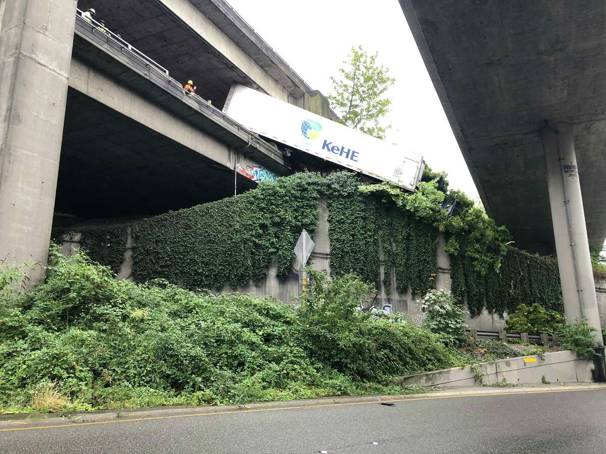 A semitractor-trailer hangs off the side of Interstate 5 on the morning of Sept. 32, 2020, after the drive collided with the barrier.
