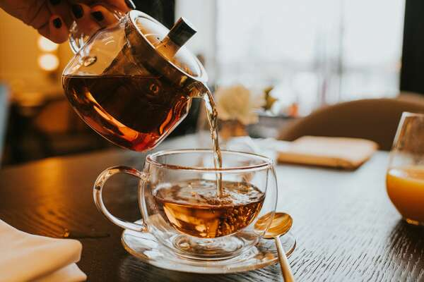 Hand pouring a cup of tea from a stylish transparent teapot into a clear cup. Spoon on side of saucer. Airy and bright image depicting morning time. Space for copy.