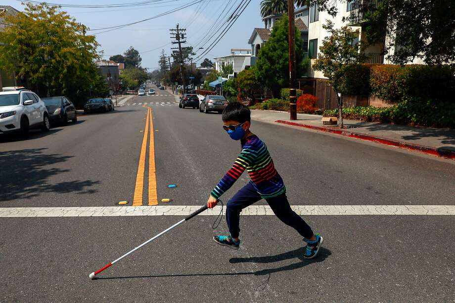 Kai Wang, 7, who is legally blind from retinal degeneration, runs across the street in Berkeley on an outing with his family during a break from distance learning. Photo: Gabrielle Lurie / The Chronicle