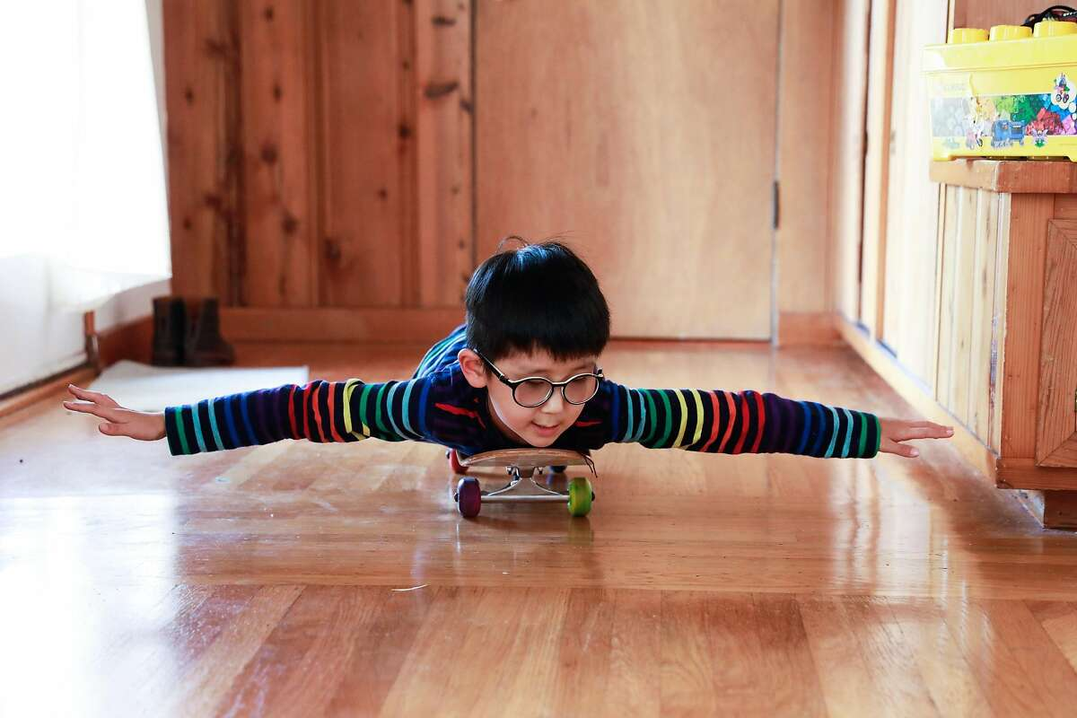 Kai Wang, 7, who is visually impaired, rides his skateboard through the house after finishing his distance learning classes in Berkeley.