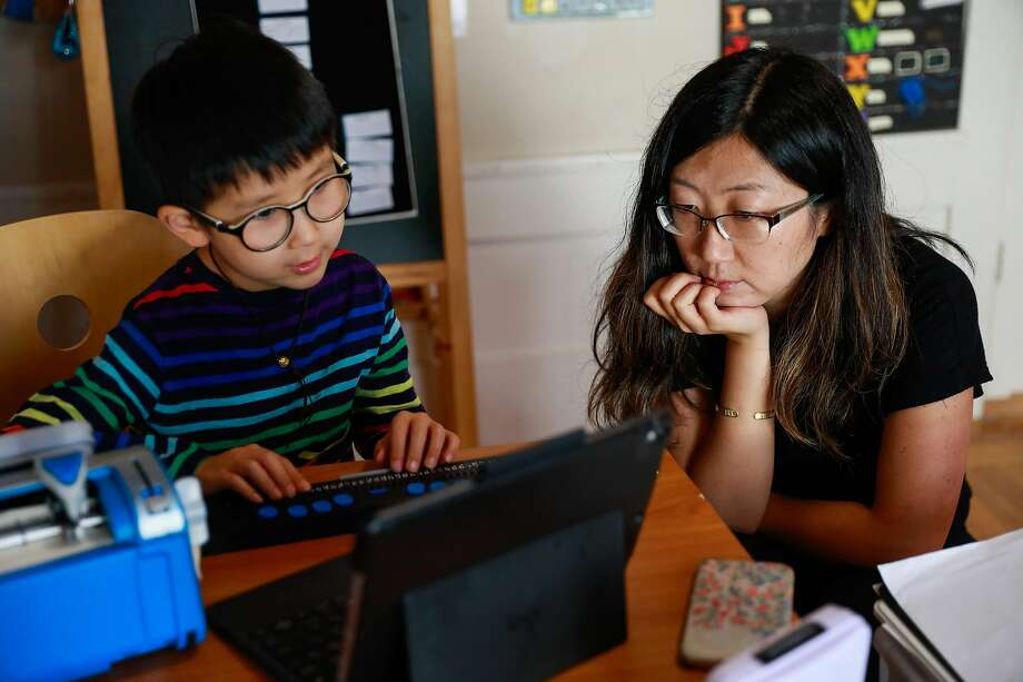 Second-grader Kai and his mom, Mina Sun, prepare for a Zoom class led by Cragmont Elementary teachers. Photo: Gabrielle Lurie / The Chronicle