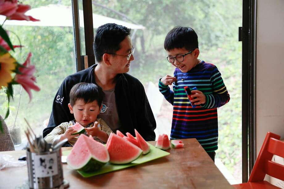 Visually impaired Kai Wang, 7, laughs with his father, Lingeng Wang, holding Kai's 2-year-old brother Skyler as they all have a snack at home in Berkeley. Photo: Gabrielle Lurie / The Chronicle