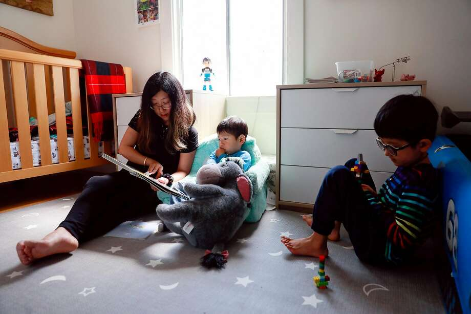 Kai Wang, 7, plays with a toy and listens to his mom Mina Sun as she reads a story to his brother Skyler before she puts him down for a nap. Photo: Gabrielle Lurie / The Chronicle