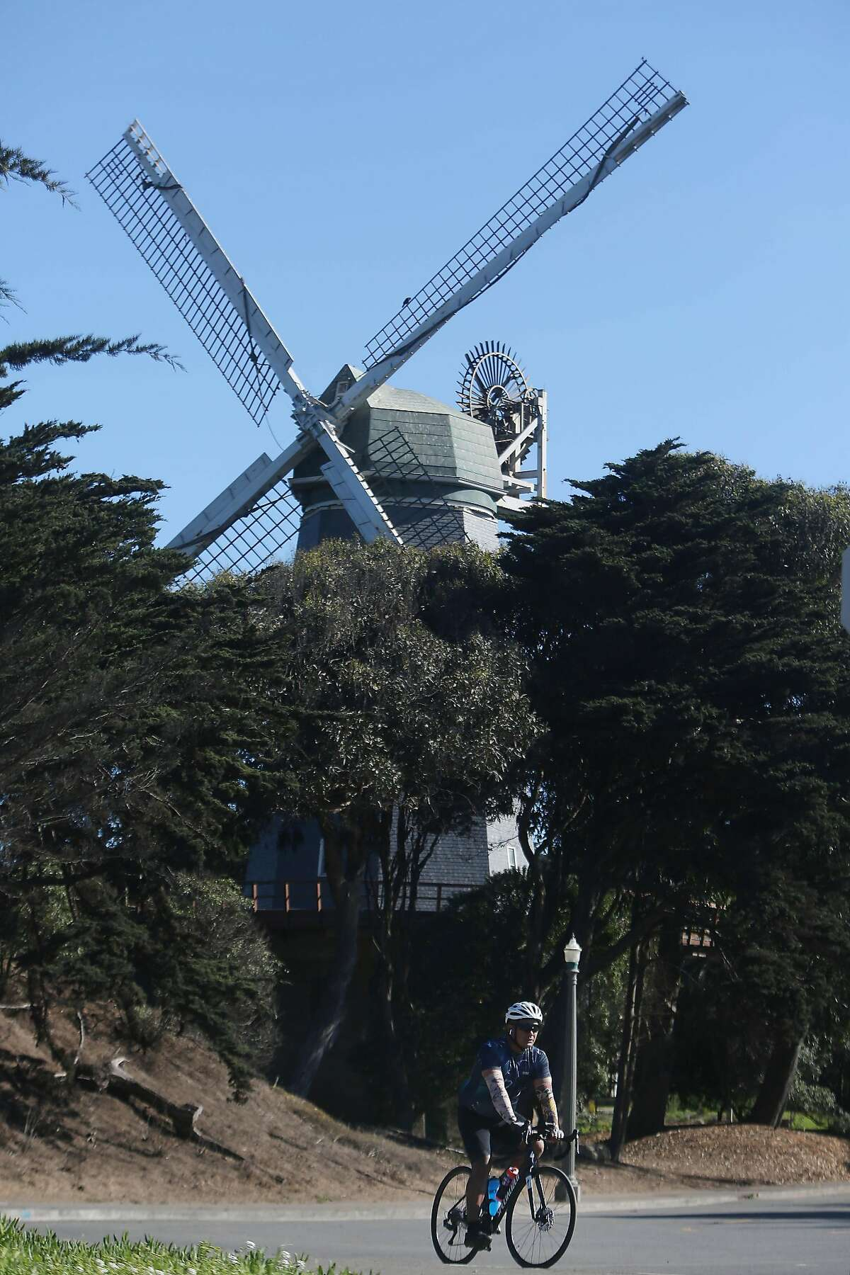 Bicyclists ride along on a slow street on MLK Drive past the Murphy Windmill in Golden Gate Park.