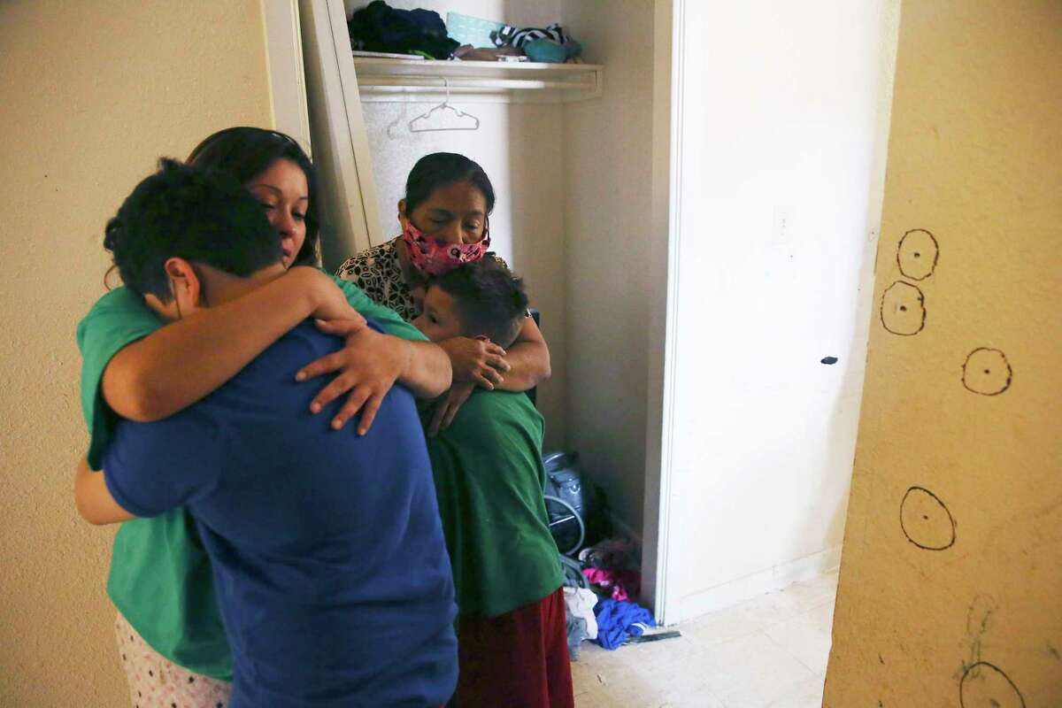 Angelic Barron, 28, left, hugs her nephew as Rose Sanchez, 66, hugs her grandson, in Barron's bullet riddled apartment on the 5600 block of Culebra Road, Wednesday, Sept. 23, 2020. San Antonio police responded to a burglary in progress call at the apartment late Tuesday. After shots were fired, Victor Sanchez, father of one of Barron's children and son of Rose Sanchez, was killed.