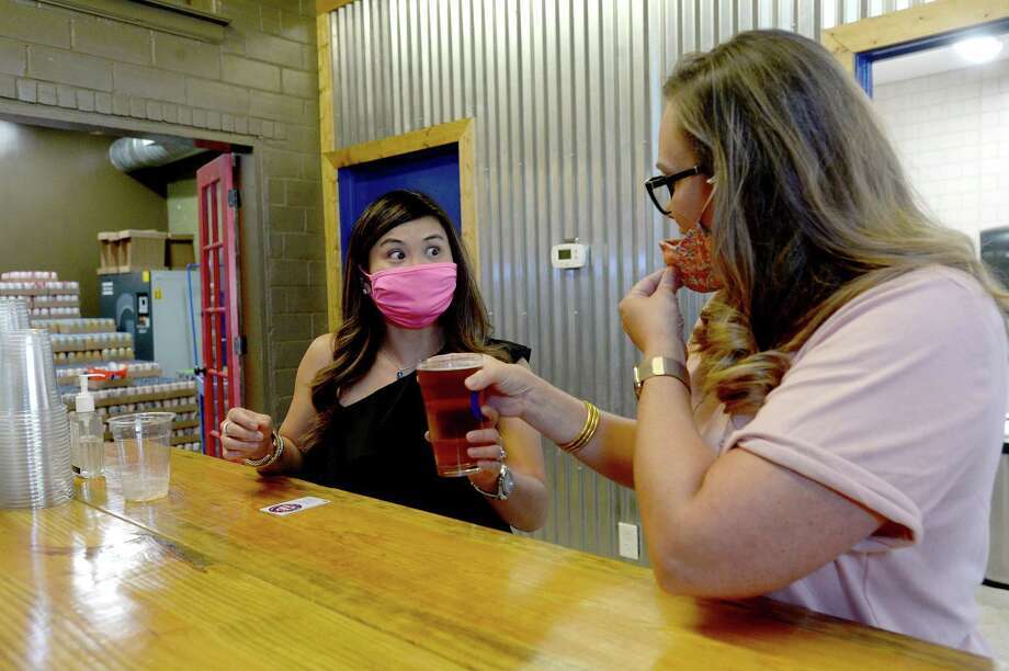 Tiffany Neale reacts after tasting her mojito flavored craft beer as she and Beth Rogers have lunch and brews at Pour Brothers Brewery in Beaumont, one of the establishments which reopened Friday after getting a license change from the TABC days ago. They and friend Lauren Martin were first timers at the downtown brewery, and said they just wanted to support local business.  Photo taken Friday, September 11, 2020 Kim Brent/The Enterprise Photo: Kim Brent / The Enterprise / BEN