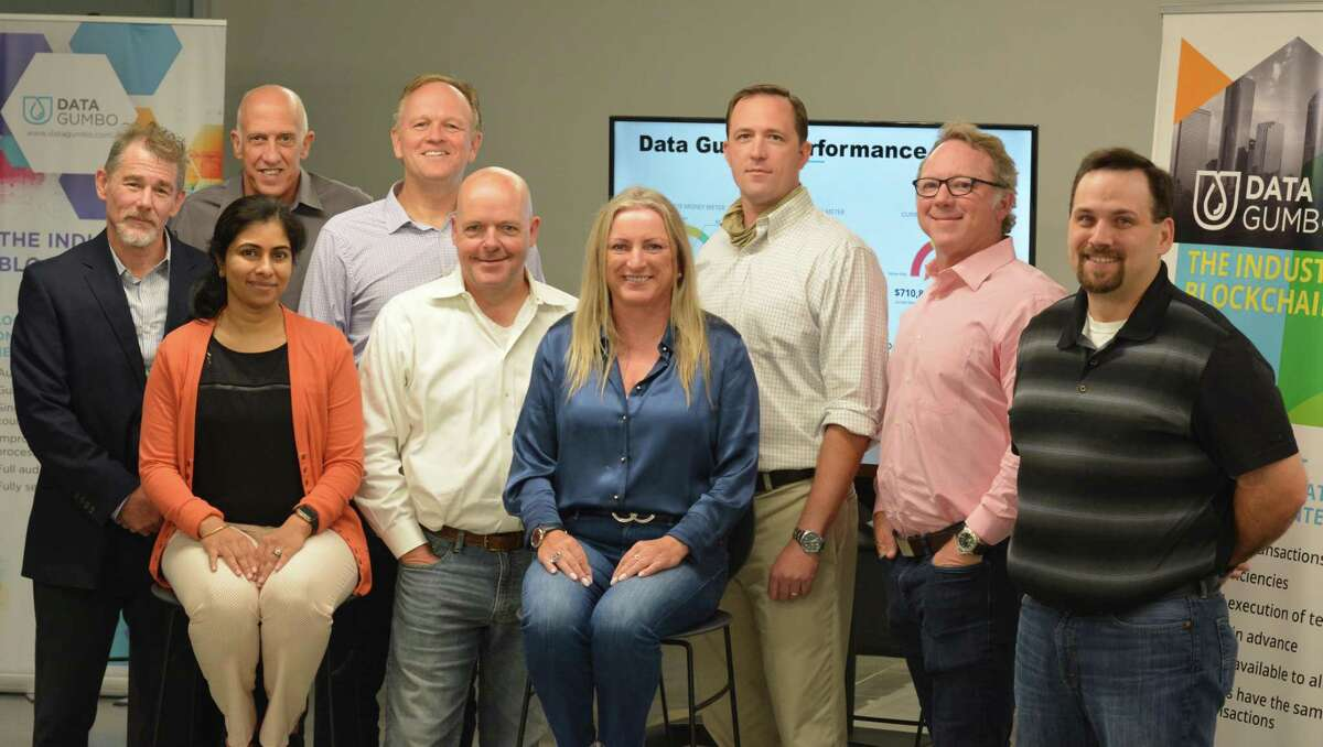 Data Gumbo CEO Andrew Bruce, second from left in the front, poses with his employees at a trade event.