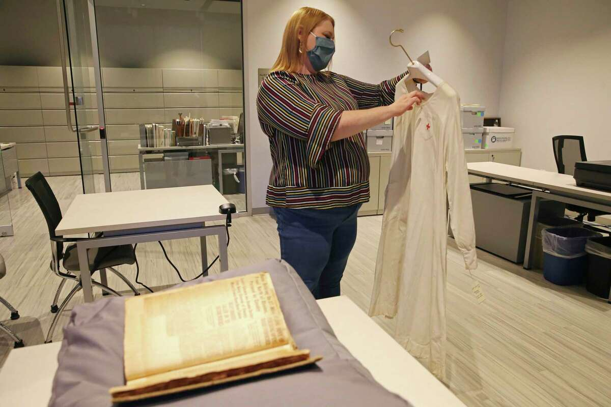 Witte Museum Chief Curator Amy Fulkerson looks at a 1918 nurse's smock by a scrapbook filled with newspaper clippings from that era. The scrapbook includes stories about the impact of the flu pandemic on San Antonio.