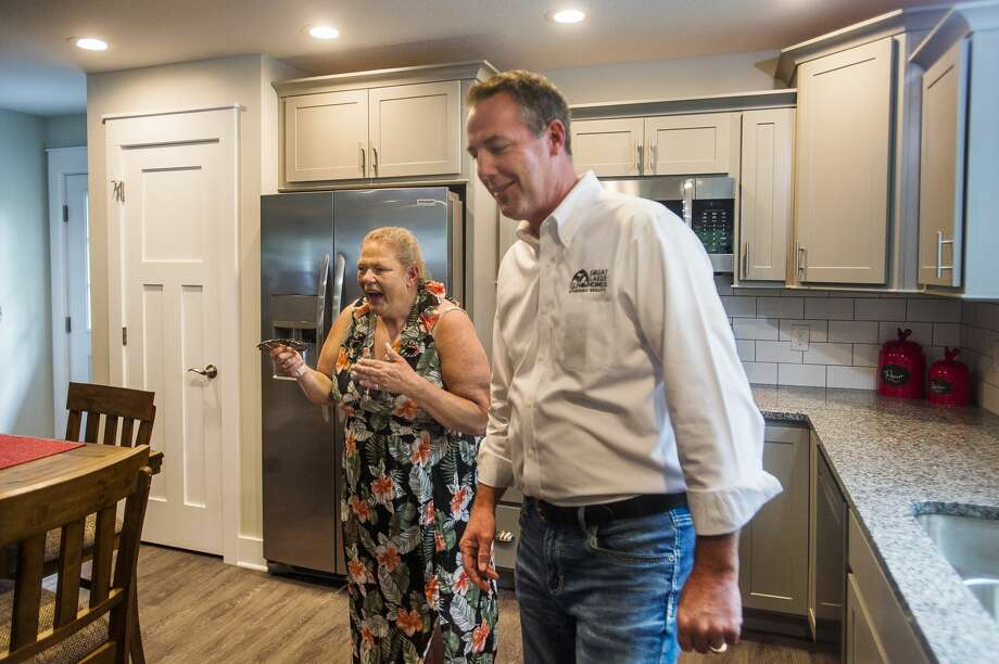 Penny Tyler, left, checks out her brand new home alongside Great Lakes Homes owner Dave Dennis, right, Wednesday, Sept. 23, 2020 in Sanford. Tyler's home was devastated by the mid-Michigan dam failures in May, and Great Lakes Homes offered to build her a new home free of charge. The Islamic Center of Midland and Midland Area Interfaith Friends furnished the home. (Katy Kildee/kkildee@mdn.net) Photo: (Katy Kildee/kkildee@mdn.net)