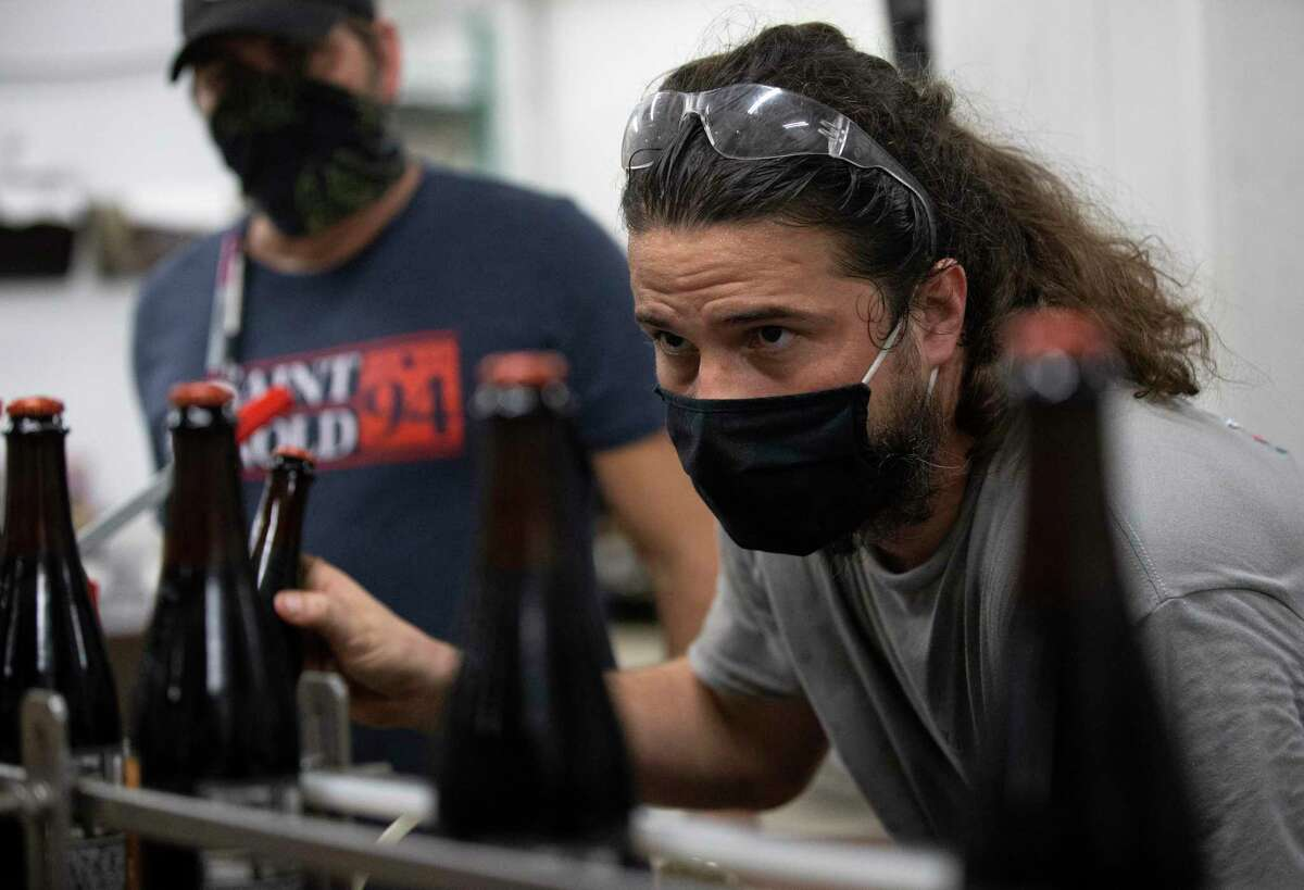 """Saint Arnold Brewing Company Packaging Team Leader Josh Day performs quality check on the """"Black Is Beautiful"""" beer Tuesday, Sept. 8, 2020, in Houston. The Black Is Beautiful beer is a limited charity beer that will benefit Fifth Ward Community Redevelopment Corporation."""