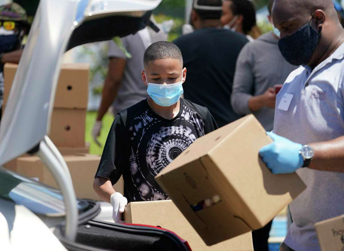 Darnell Joseph, 13, and other volunteers load boxes into a car during a COVID-19 essentials distribution at Missouri City Baptist Church June 13. Food, masks, hand sanitizer and educational materials were distributed at the joint event presented by Mayor Sylvester Turner's Health Equity Response Task Force Medical Care Subcommittee and the Houston Medical Forum.