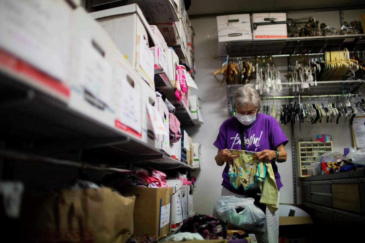 Emergency Aid Coalition volunteer Linda Davenport, 85, organizes clothing intended for people in need of newer apparel.