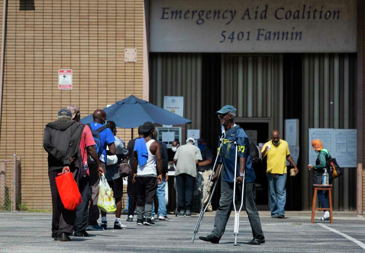 People form a line outside of Emergency Aid Coalition to pick up brown bag lunches.