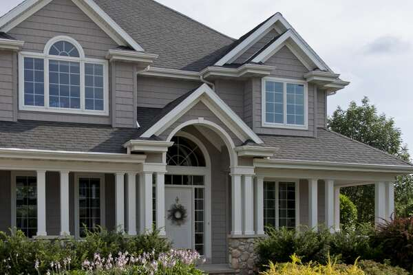 The front of a beautiful luxury home in a typical suburban neighborhood.