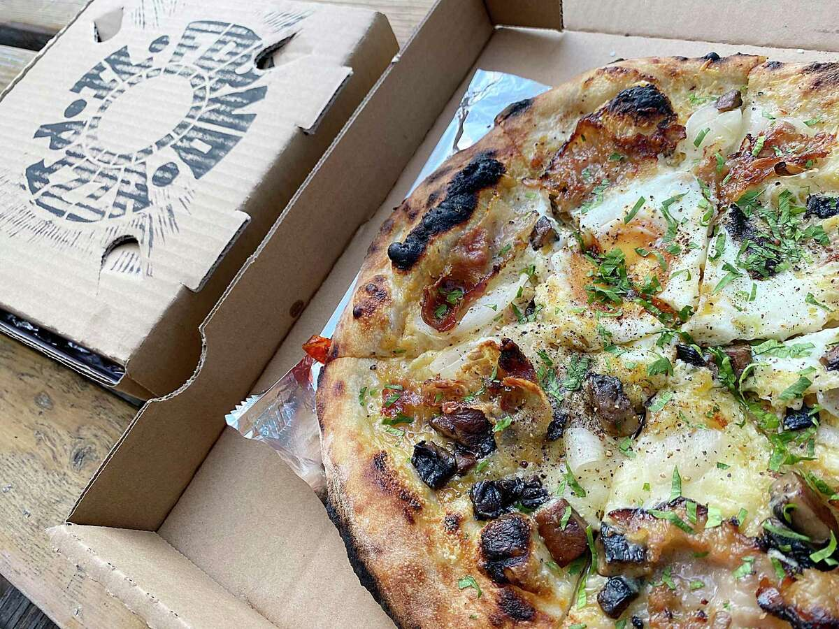 The Carbonara pizza comes with guanciale, mushrooms, egg, roasted onion and garlic at Il Forno.