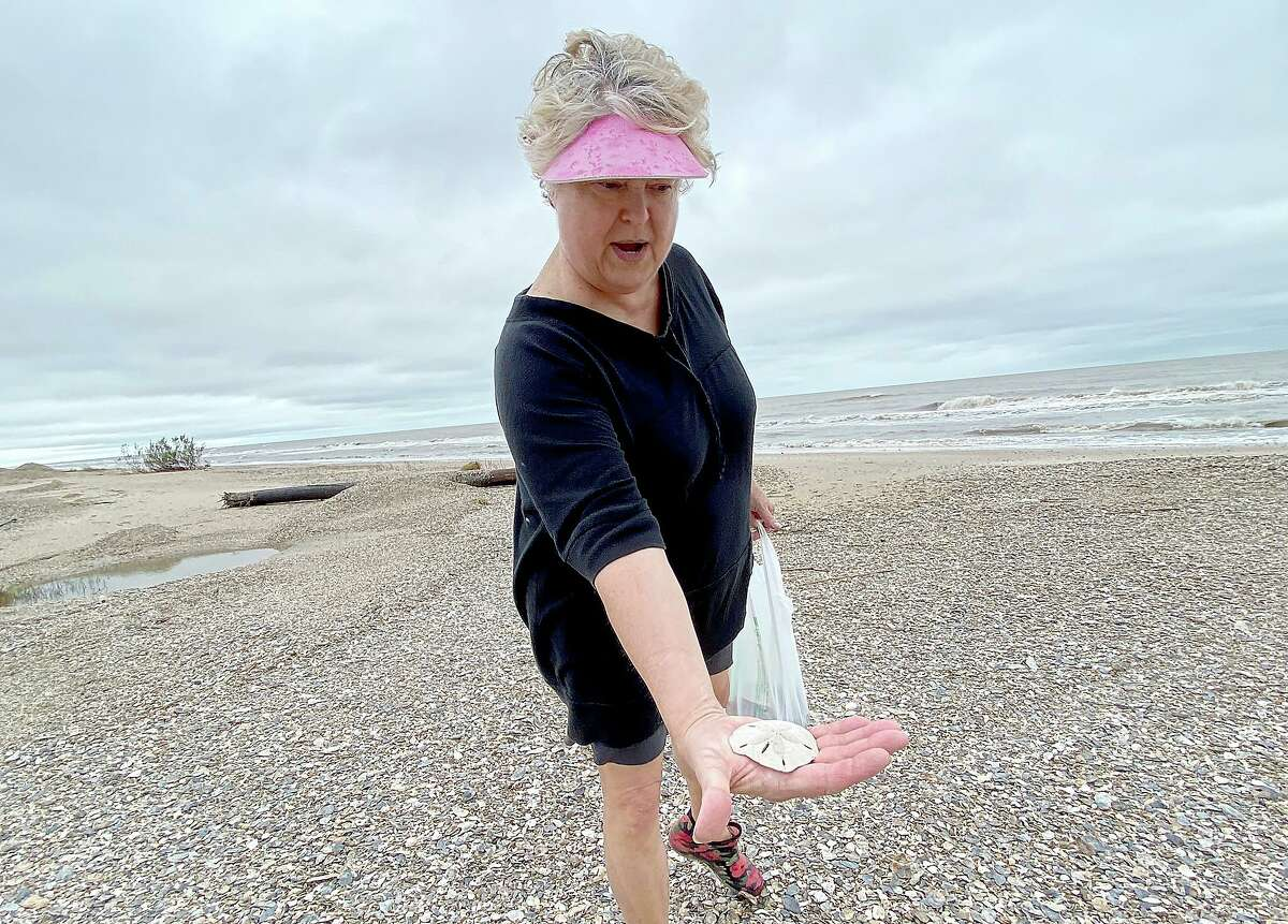 Patti Castille shows the first sand dollar she has ever found as she searches for treasures washed up in the wake of high tides and churning Gulf waters on the Bolivar Peninsula Wednesday. Castille has been a resident of the peninsula for 10 years and says her family stayed put this week as Tropical Depressionn made its way up the coast.