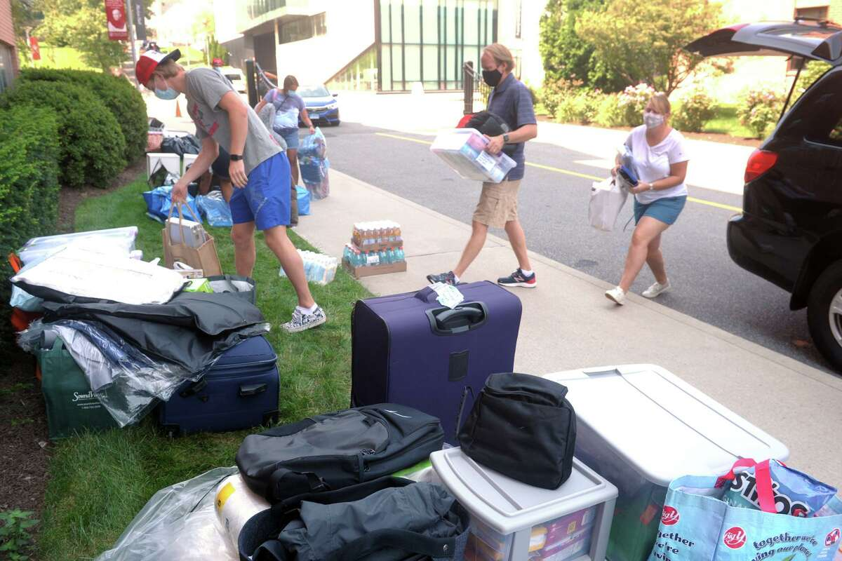 Freshmen students and their families unload their belonging outside of a dormitory on the campus of Sacred Heart University, in Fairfield, Conn. Aug. 25, 2020.
