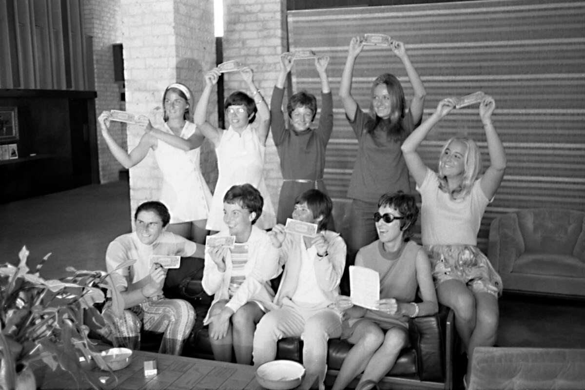 In this Sept. 23, 1970, photo provided the Houston Library, tennis players hold up $1 bills after signing a contract with World Tennis magazine publisher Gladys Heldman to turn pro and start the Virginia Slims tennis circuit. From left standing are: Valerie Ziegenfuss, Billie Jean King, Nancy Richey and Peaches Bartkowicz. From left seated are: Judy Tegart Dalton, Kerry Melville Reid, Rosie Casals, Gladys Heldman and Kristy Pigeon. Gladys Heldman replaced her daughter, Julie Heldman, who was injured and unable to pose for the 1970 photo. Ita€™s the 50th anniversary of Billie Jean King and eight other women breaking away from the tennis establishment in 1970 and signing a $1 contract to form the Virginia Slims circuit. That led to the WTA Tour, which offers millions in prize money. (Bela Ugrin/Courtesy Houston Library via AP)