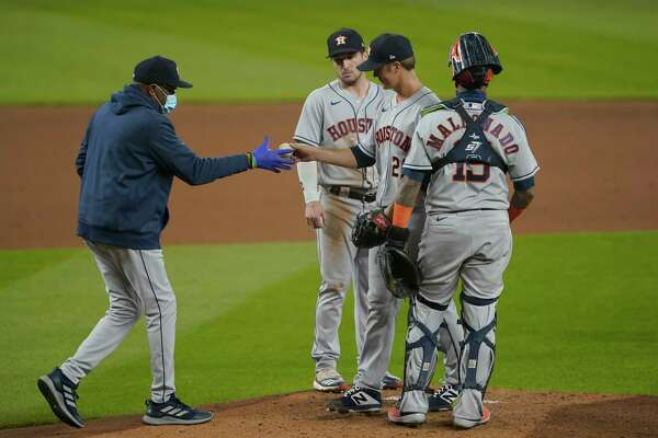 Houston Astros starting pitcher Zack Greinke, second from right, is pulled from a baseball game against the Seattle Mariners by manager Dusty Baker Jr., left, during the fifth inning of a baseball game, Wednesday, Sept. 23, 2020, in Seattle. (AP Photo/Ted S. Warren)