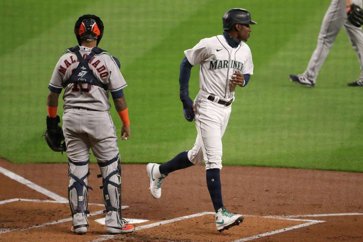 SEATTLE, WASHINGTON - SEPTEMBER 23: Kyle Lewis #1 scores off an RBI double by Ty France #23 of the Seattle Mariners to take a 1-0 lead in the first inning against the Houston Astros at T-Mobile Park on September 23, 2020 in Seattle, Washington.