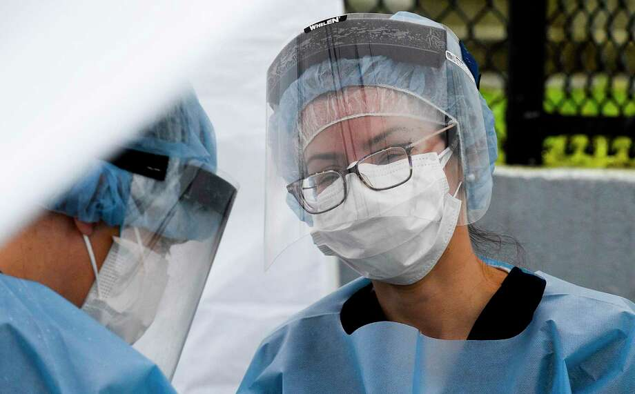 Nurse Practitioner Julianna Barresi, APRN, at right, face shield fogs up as she waits to tests people who have made appointments to be tested for the Coronavirus at the Family Center at Wilbur Peck Court in Greenwich, Connecticut on May 1, 2020. Some 60 Rapid Covid-19 test were performed, yielding results in less than a day. Photo: Matthew Brown / Hearst Connecticut Media / Stamford Advocate
