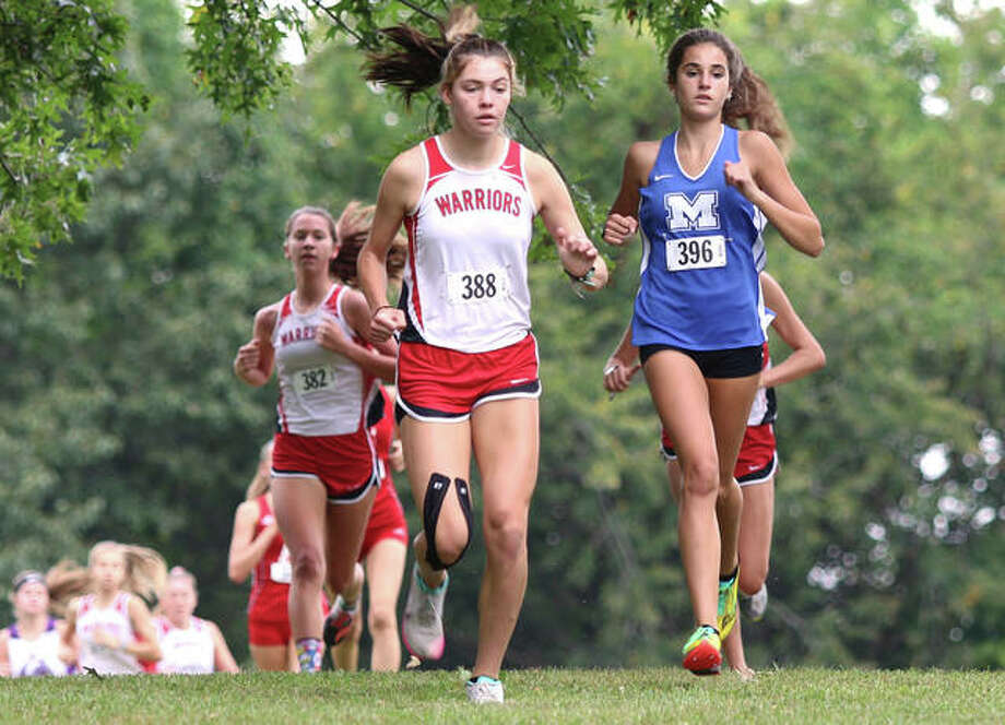 Marquette Catholic's Kailey Vickrey (right) runs with Granite City's Claire Sykes (388) in the opening mile Wednesday in the Alton Invitational cross country meet at Moore Park in Alton. Sykes placed second in the girls race, with Vickrey in third. Photo: Greg Shashack / The Telegraph