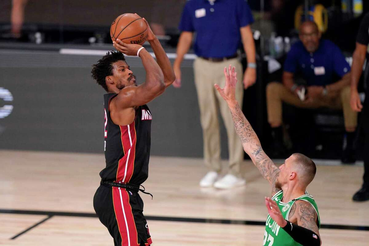 Miami Heat forward Jimmy Butler left, takes a shot at the basket over Boston Celtics' Daniel Theis, right, during the first half of Game 4 of an NBA basketball Eastern Conference final, Wednesday, Sept. 23, 2020, in Lake Buena Vista, Fla. (AP Photo/Mark J. Terrill)