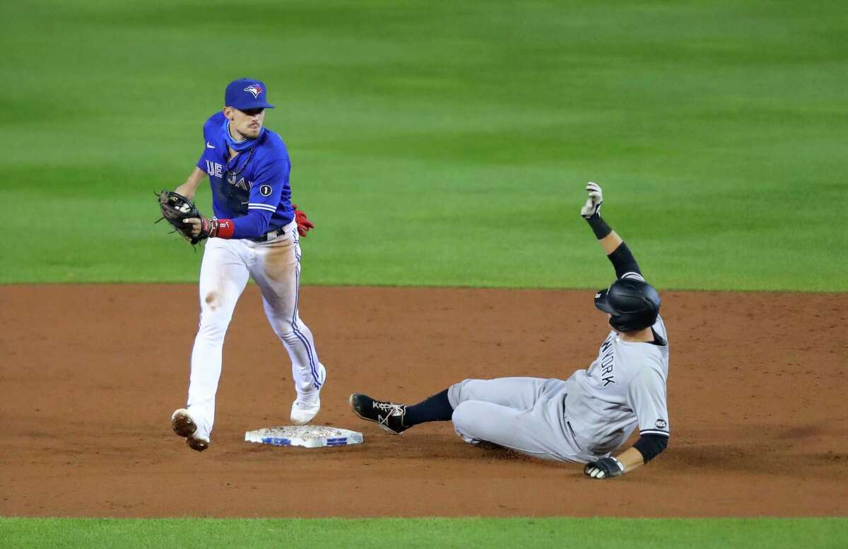 BUFFALO, NY - SEPTEMBER 23: Cavan Biggio #8 of the Toronto Blue Jays tags the base for an out as DJ LeMahieu #26 of the New York Yankees slides during the third inning at Sahlen Field on September 23, 2020 in Buffalo, New York. The Blue Jays are the home team due to the Canadian governments policy on COVID-19, which prevents them from playing in their home stadium in Canada. (Photo by Timothy T Ludwig/Getty Images)