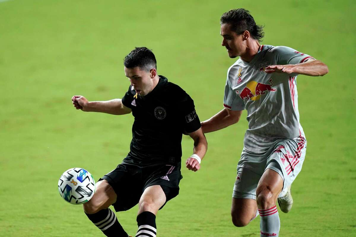 Inter Miami midfielder Lewis Morgan, left, and New York Red Bulls midfielder Aaron Long, right, go for the ball during the first half of an MLS soccer match, Wednesday, Sept. 23, 2020, in Fort Lauderdale, Fla. (AP Photo/Lynne Sladky)