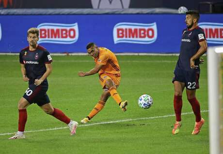 Mauro Manotas of the Dynamo shoots between Gaston Gimenez and Mauricio Pineda of the Chicago Fire, who won 4-0.