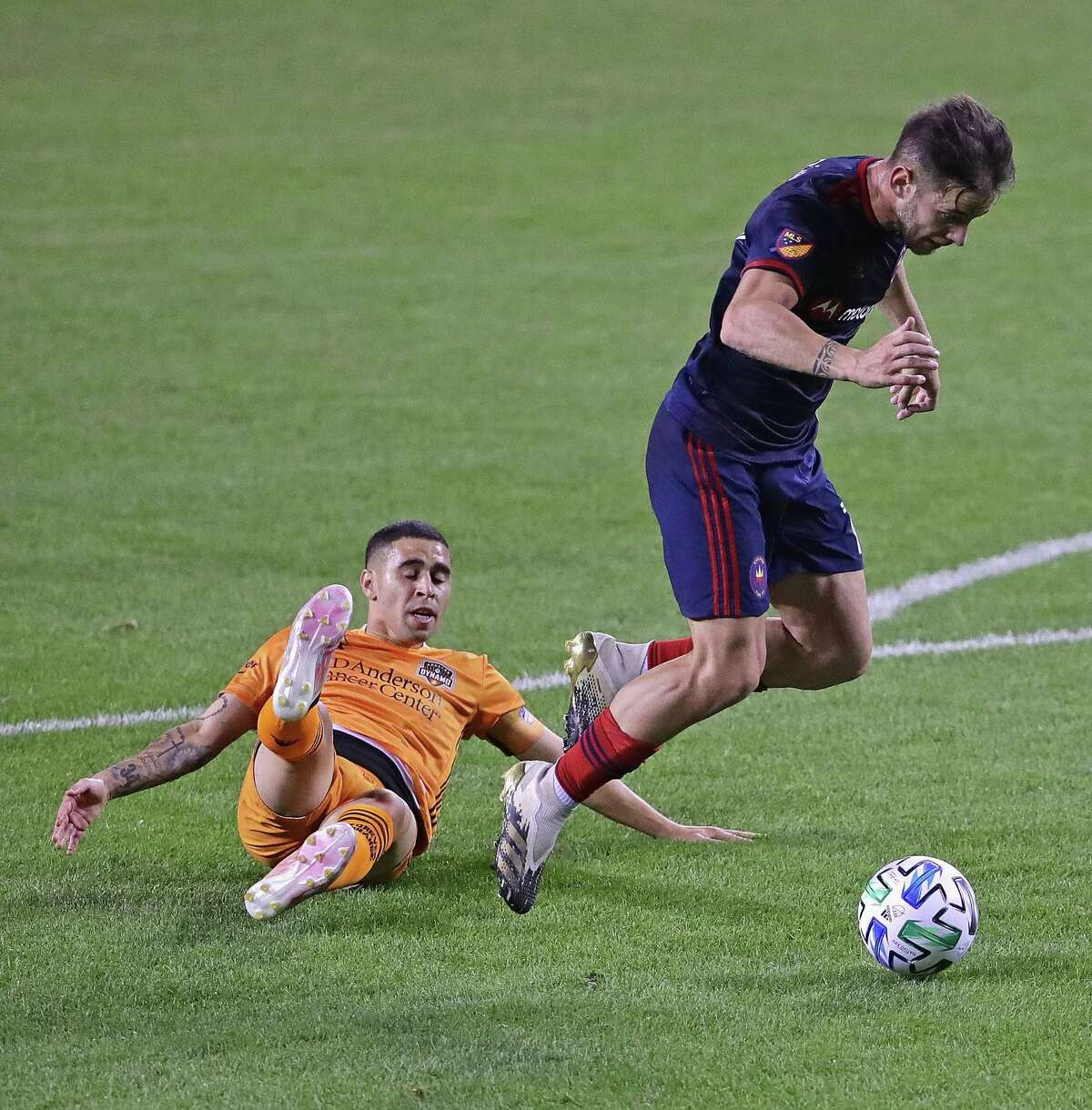 CHICAGO, ILLINOIS - SEPTEMBER 23: Alvaro Medran #10 of Chicago Fire FC gets over Matias Vera #22 of Houston Dynamo on his way to scoring a goal at Soldier Field on September 23, 2020 in Chicago, Illinois.