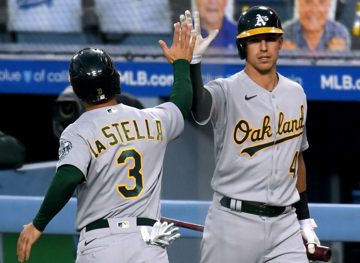 LOS ANGELES, CALIFORNIA - SEPTEMBER 23: Tommy La Stella #3 of the Oakland Athletics celebrates his run with Jake Lamb #4, to take a 1-0 lead over the Los Angeles Dodgers, during the first inning at Dodger Stadium on September 23, 2020 in Los Angeles, California. (Photo by Harry How/Getty Images)