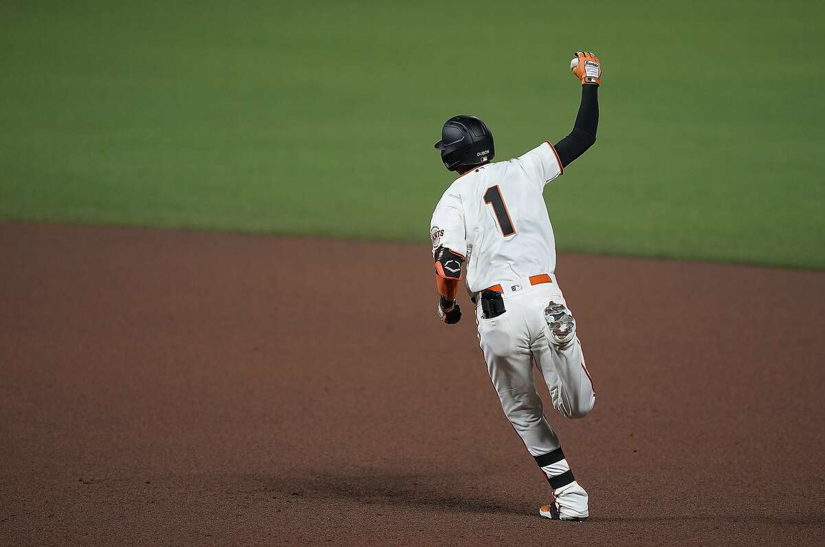 San Francisco Giants' Mauricio Dubon raises his arm as he runs the bases after hitting a three-run home run against the Colorado Rockies during the fifth inning of a baseball game Wednesday, Sept. 23, 2020, in San Francisco. (AP Photo/Tony Avelar)