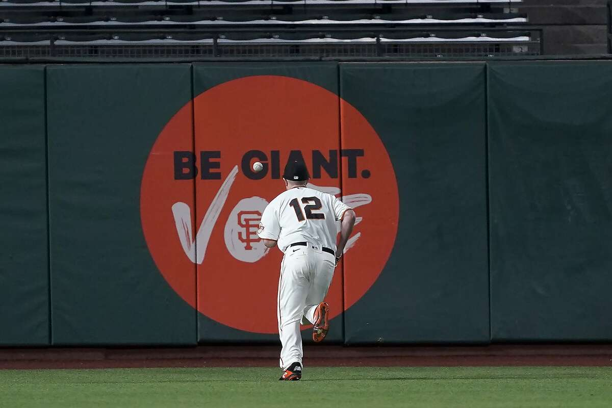 San Francisco Giants left fielder Alex Dickerson chases down a double by Colorado Rockies' Raimel Tapia during the fifth inning of a baseball game Wednesday, Sept. 23, 2020, in San Francisco. (AP Photo/Tony Avelar)