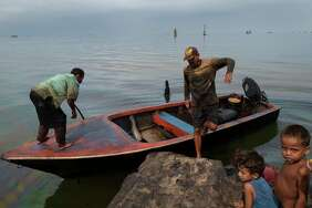 Fishermen Omar González, left, and Raúl Silva, center, dock their fishing boat on the oil-covered shores of Lake Maracaibo in May 2019.