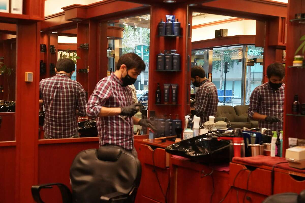 At Ahmet's Barber & Hair Styling in San Francisco, Iggy Ibrahimli prepares for clients. Reopening in the Bay Area and elsewhere has not yet had a significant impact on California's unemployment claims.