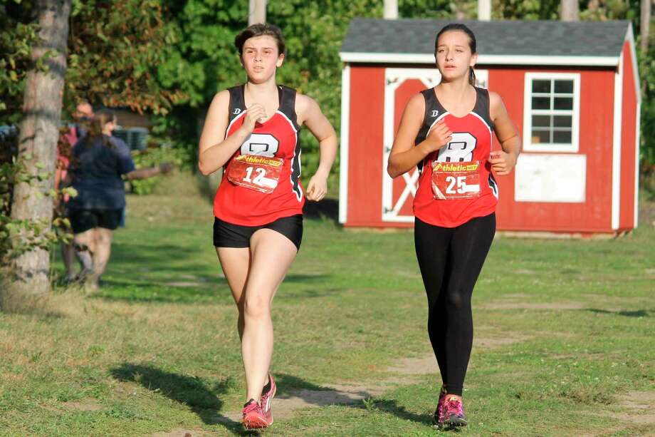 Victoria Hall (left) and Jocelyn Teter (right) race side by side in their home conference meet on Tuesday. (Photo/Robert Myers)