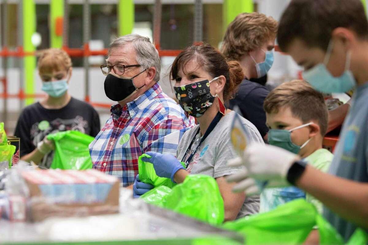 Volunteers help pack packages at the Houston Food Bank.