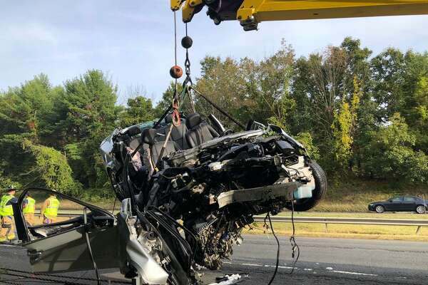 A Chevrolet sedan is lifted out of a wooded area off the shoulder of eastbound I-84 near Exit 8 the morning of Sept. 24, 2020.